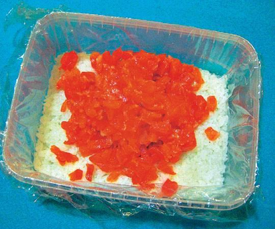 1. Первый этап - подготовка ингредиентов. Рис нужно отварить до готовности, яйца - вкрутую, морковь - до мягкости. Дно удобной емкости застелить пищевой пленкой и выложить рис ровным слоем. При желании в рецепт приготовления красной рыбы под шубой салата можно использовать немного рисового уксуса, как для роллов.