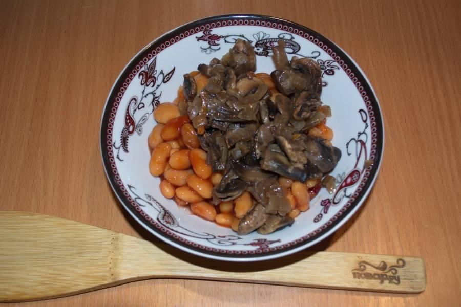 На растительном масле обжарьте лук, добавьте к нему грибы шампиньоны. Жарьте все вместе до готовности. Грибы переложите в миску с фасолью.