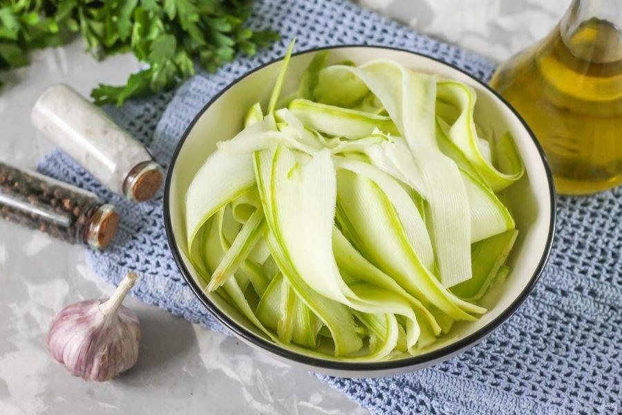 Промойте молодой кабачок или несколько овощей в воде, срежьте хвостики и нарежьте плоды лентами с помощью овощечистки.