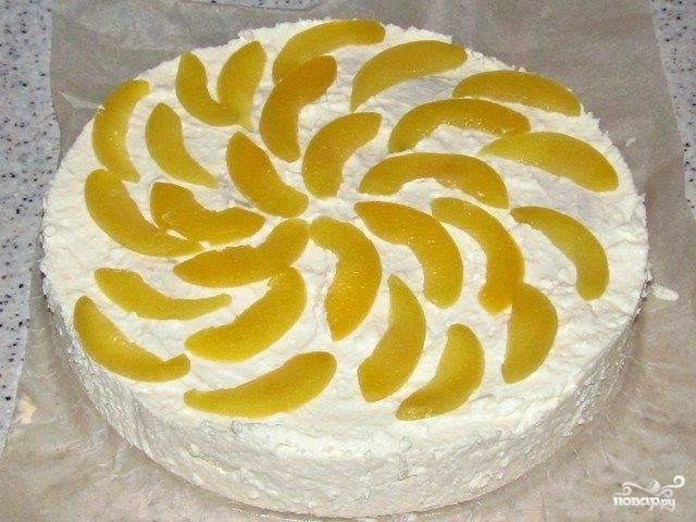 Уложите на торт второй слой бисквита и намажьте его кремом. Консервированный персик порежьте одинаковыми дольками и красиво уложите сверху на крем. Поставьте торт в холод на час, а затем снимите разъёмную форму.