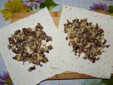 Лаваш разделить на квадратики и выложить начинку, посыпать тертым сыром.