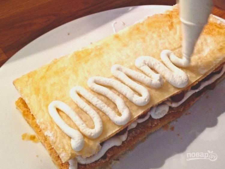 3.Достаньте противень и разрежьте тесто на 3 части. Выложите 1/3 части, смажьте кремом, выложите ягоды малины, накройте второй частью.