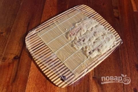 Возьмите коврик для роллов. Сверху выложите пластиковую плёнку. Разложите на ней филе.
