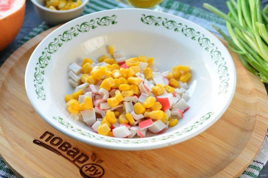 В миске смешайте крабовые палочки и консервированную кукурузу.
