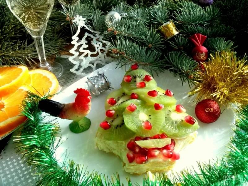 Украсьте елочку кольцами киви и зернами граната, при желании присыпьте кокосовой стружкой. Поставьте десерт в холодильник минимум на полчаса. Приятного аппетита!