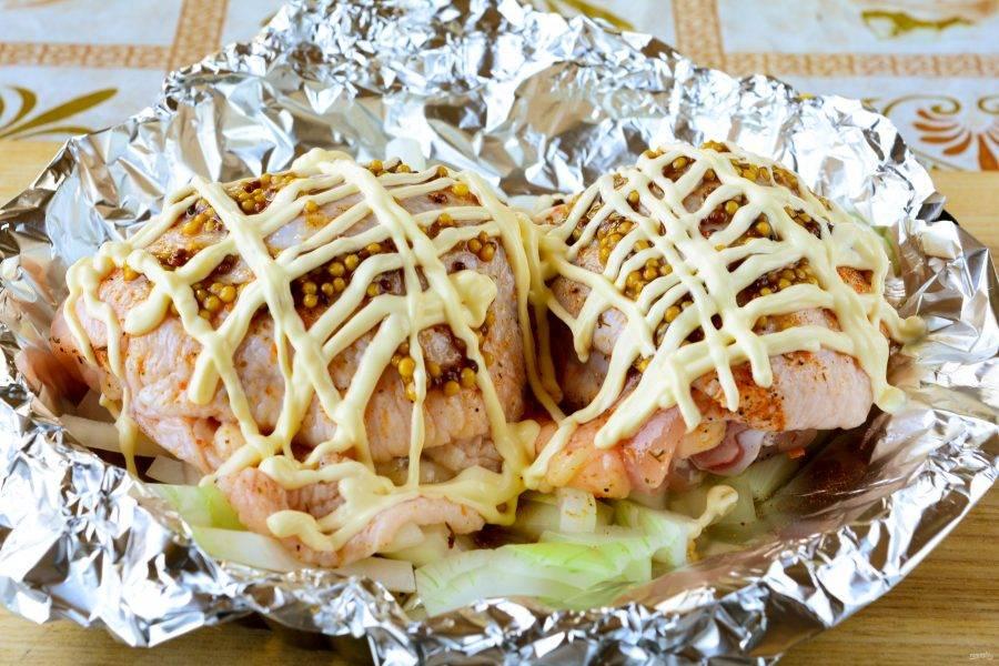 Куриные бедрышки полейте майонезом и отправьте запекаться в разогретую до 180 градусов духовку.