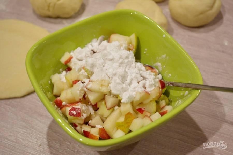 Приготовьте начинку. Она может быть любой.  Я готовила пирожки с яблоком. Для начинки нужно вымыть яблоки и нарезать на маленькие кубики. В начинку добавьте кукурузный крахмал. При запекании он удержит фруктовый сок в пирожке. Сахар в начинку не кладите. Сахара можно насыпать непосредственно при формовке пирожка.