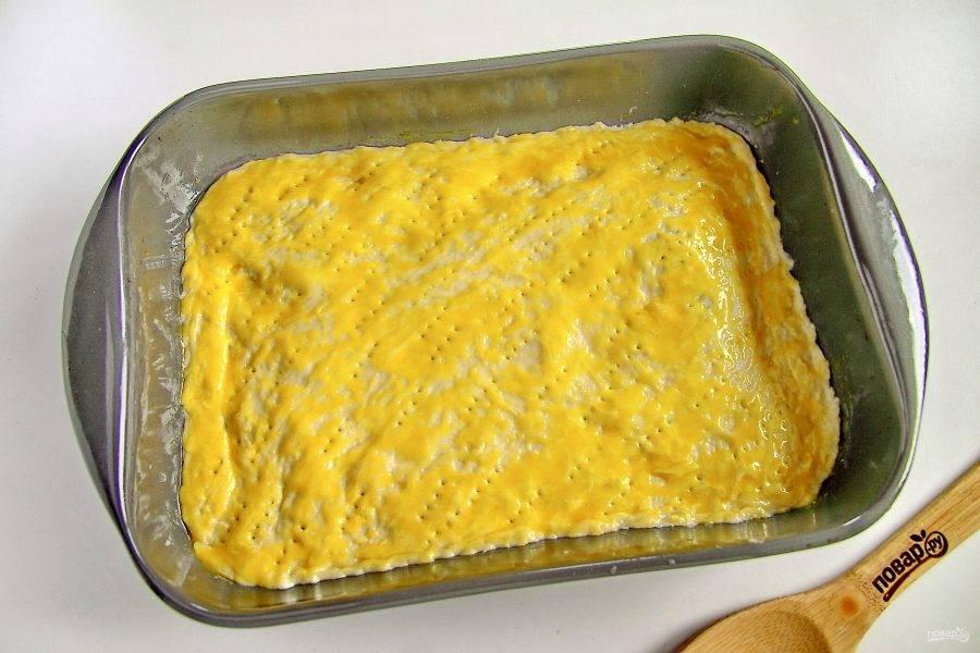 Накройте начинку второй частью теста. Сделайте по всей поверхности проколы вилкой и смажьте тесто желтком. Готовьте в духовке при температуре 200 градусов около 35 минут.