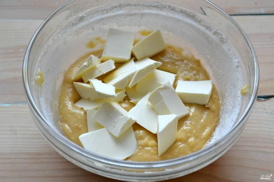 Добавьте размягченное и порезанные кусочками сливочное масло. Хорошо размешайте и замесите мягкое элластичное тесто.
