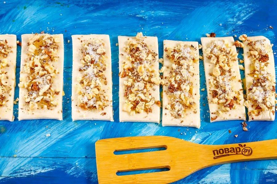 Обмажьте слоеные ломтики взбитым куриным яйцом и присыпьте смесью из сахара и орехов сверху.