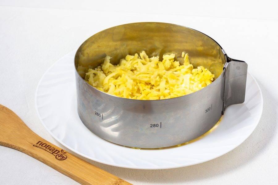 С помощью кулинарного кольца диаметром 16 см. начнем выкладывать салат слоями. Первый слой - натертый на крупной терке картофель и майонез.