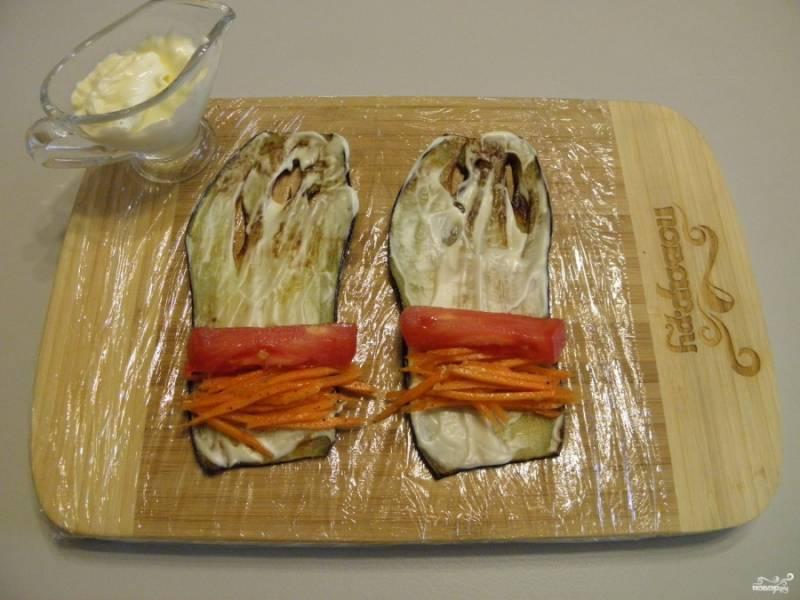 На каждый листочек баклажана положите по чуть-чуть морковки корейской и по ломтику помидора.