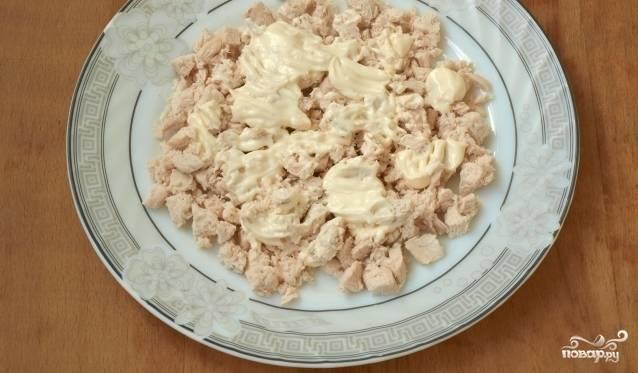 Нарежьте кусочками куриное филе, уложите его первым слоем в салатницу. Промажьте его заправкой.