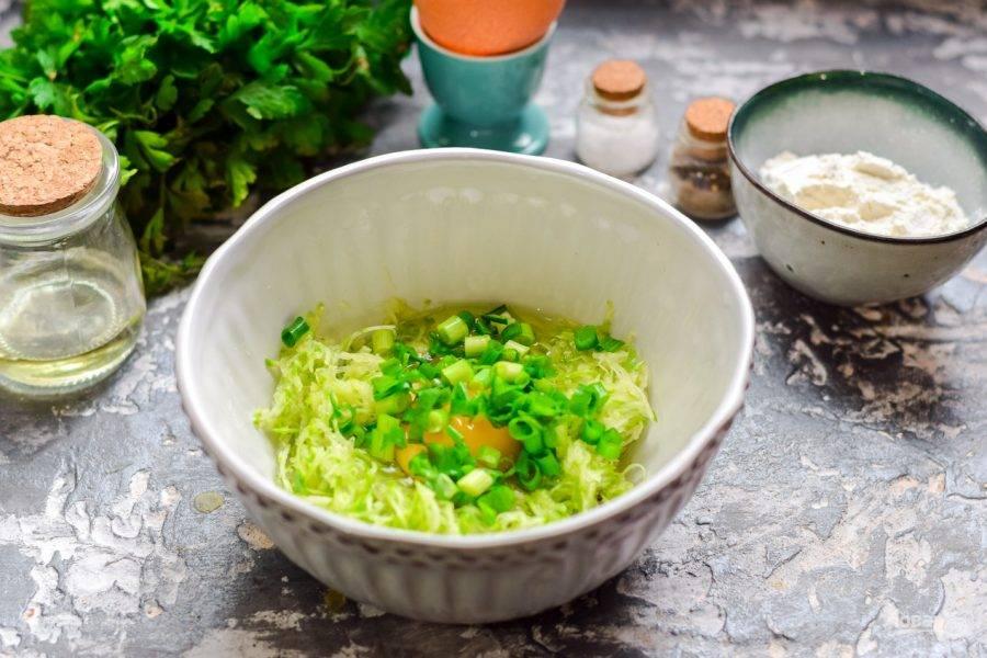 Зеленый лук ополосните и просушите, нарежьте мелко и добавьте к кабачкам.