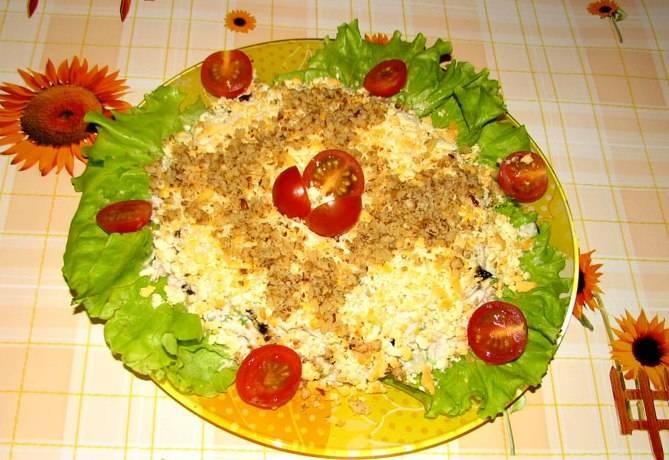 Листья салата вымыть, обсушить и выложить на плоское блюдо. По центру выкладываем заправленный салат, посыпаем его желтками и оставшимися грецкими орехами. Украшаем и подаем к столу.