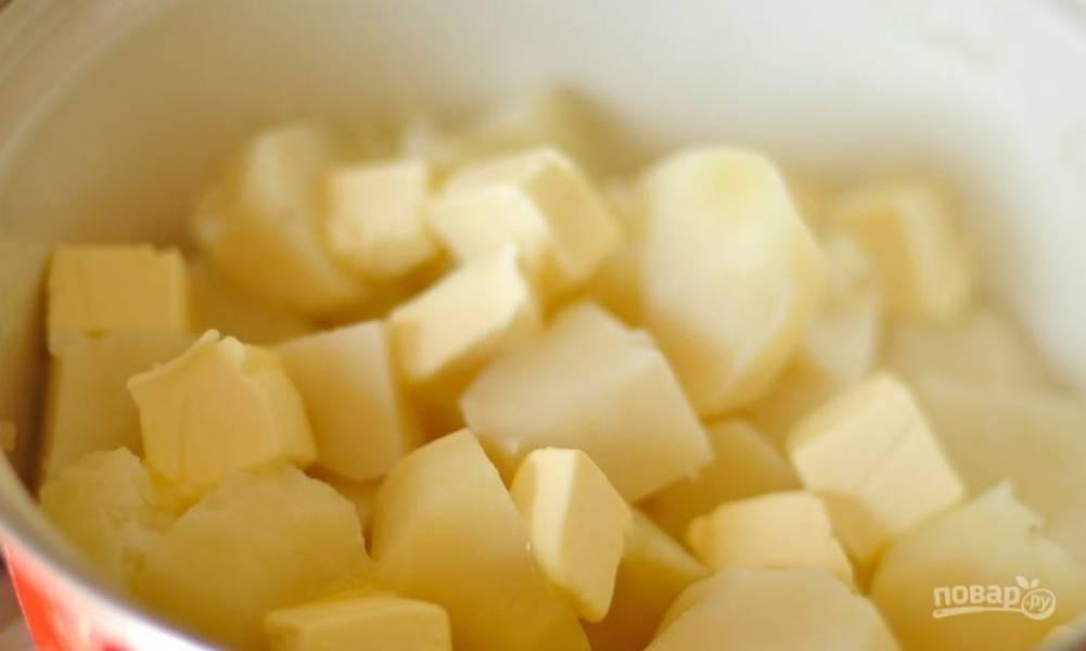 Когда картофель будет готов, слейте с него жидкость и влейте в кастрюлю молоко. Затем нарежьте масло на куски и добавьте к картофелю с молоком.