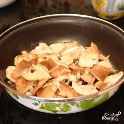 Первое, что делаем - мелко рубим чеснок, а у грибов удаляем ножки. Обжариваем чеснок с грибами в сковороде до румяности.