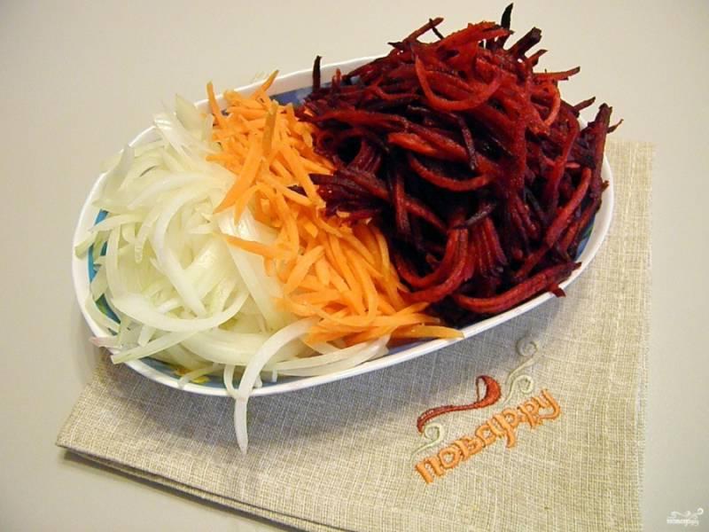 Очистите овощи. Порежьте лук полукольцами. свеклу и морковь натрите на крупной квадратной терке. Воду для супа поставьте на огонь и доведите до кипения.