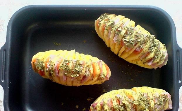 В каждый надрез на картофеле вкладываем чеснок, морковь и ветчину. Смазываем картофель маслом, присыпаем специями и выкладем на противень. Выпекаем в духовке 1 час, температура 200 градусов.