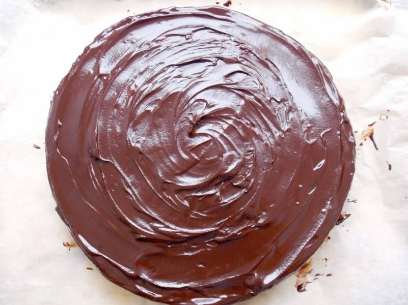 Извлеките торт из холодильника и полностью покройте его шоколадной глазурью.