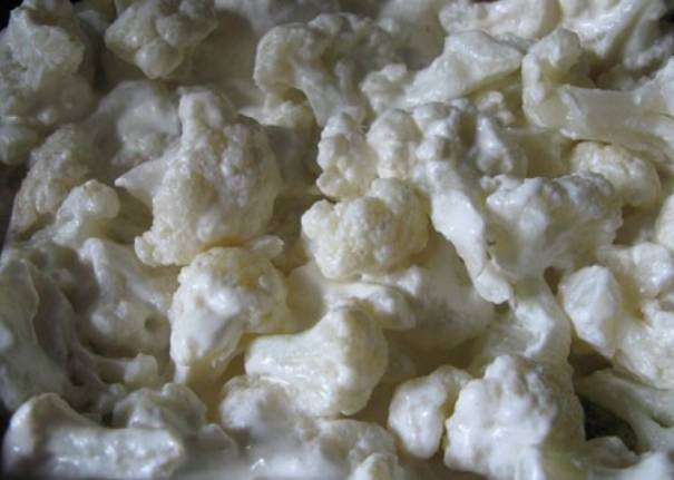 Смешиваем сливки со сметаной и заливаем полученной смесью капусту. Солим и перемешиваем, готовим еще 3-4 минуты.