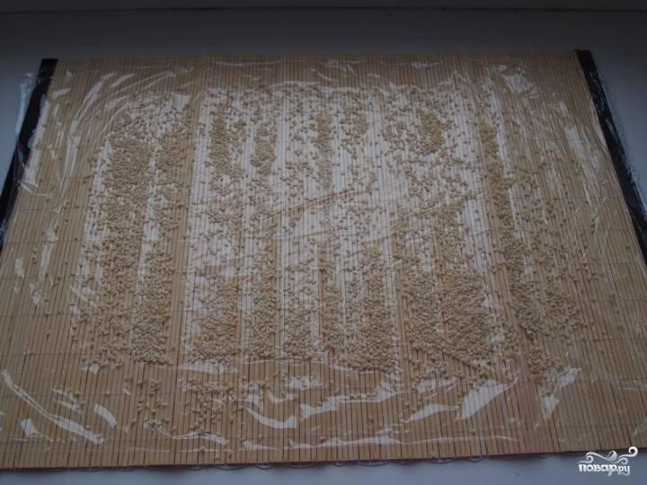 2.Бамбуковый коврик для приготовления суши застилаем пищевой пленкой, посыпаем кунжутными семенами.