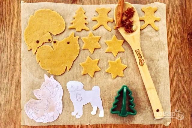 Тесто разделите на четыре части, раскатайте на пергаменте в тонкий пласт толщиной 0,5 см. Вырубите печенье с помощью формочек или вырежьте с помощью трафарета из бумаги. На этот Новый год я заранее вырезала фигурки собак. Если хотите повесить печенье на елку, то сделайте дырочку с помощью коктейльной трубочки. Поставьте печенье запекаться в разогретую до 180 °С духовку на 10-12 минут.