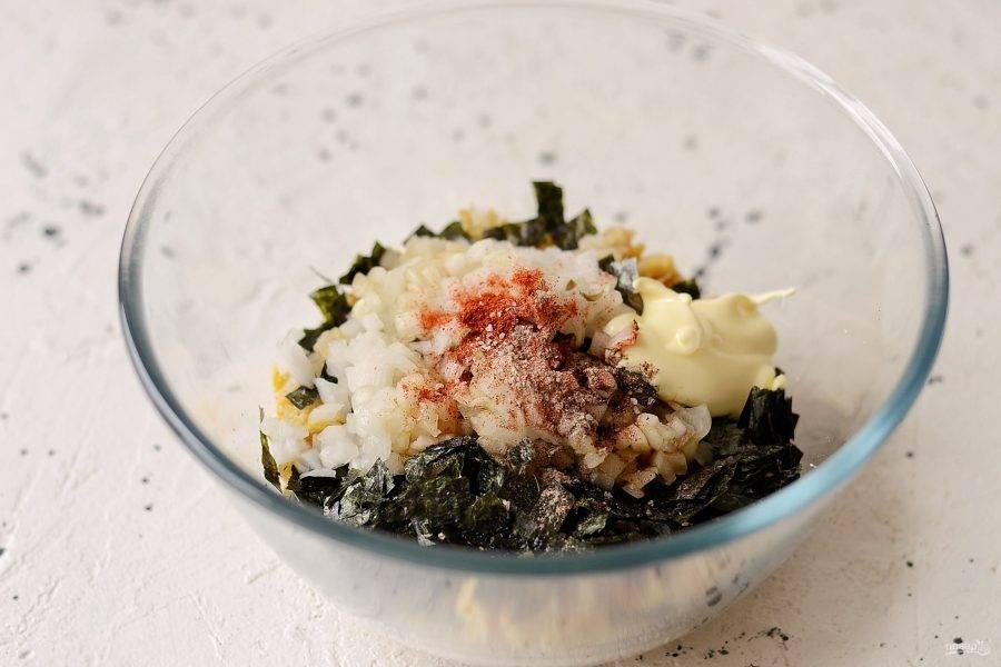 Соедините вместе нут, каперсы, огурцы, водоросли и лук. Добавьте соль, рыбную приправу, перец и копченую паприку. Заправьте салат соевым соусом и постным майонезом.