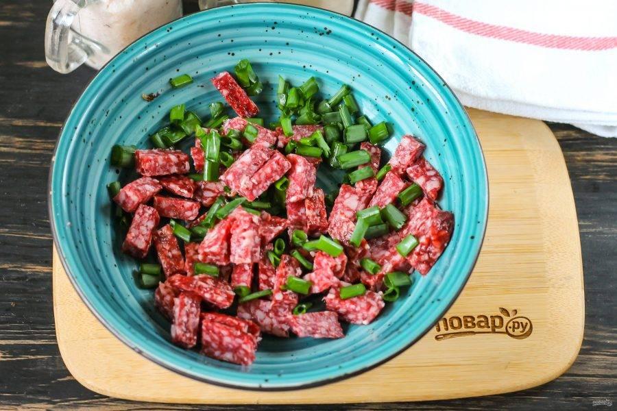 Копченую колбасу, ветчину или отварное мясо нарежьте брусочками. Промойте перья зеленого лука, измельчите и высыпьте в глубокую емкость вместе с колбасной нарезкой.
