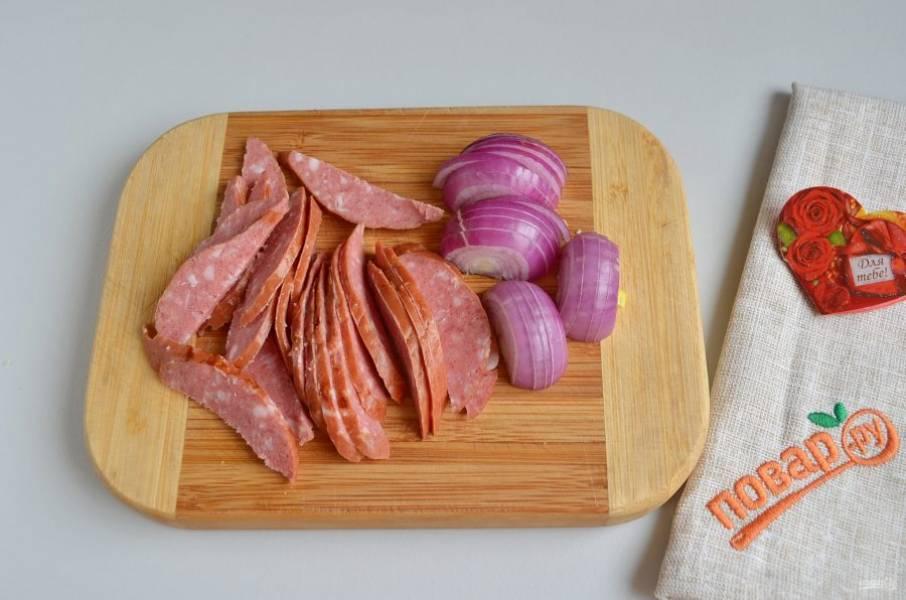 2. Очистите лук, порежьте его полукольцами, колбаску соломкой или дольками, можно полудольками, как нравится.