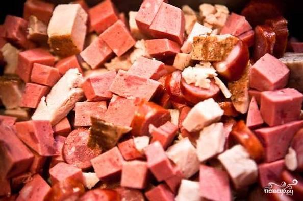 2. Следом отправьте нарезанные сосиски и выложите все мясные деликатесы в жаропрочную форму. Отправьте в разогретую до 200 градусов духовку.
