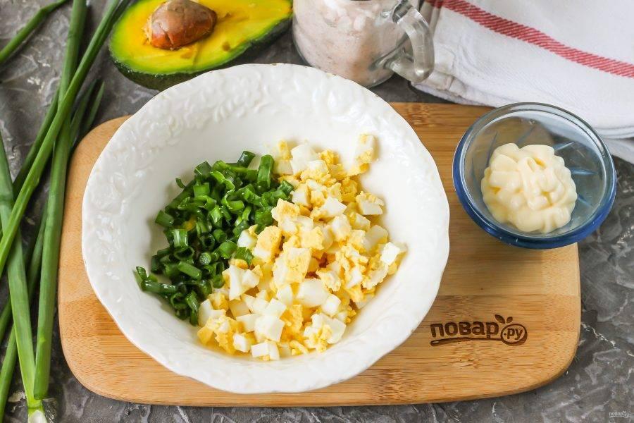 Отварное куриное яйцо очистите от скорлупы, промойте в воде и нарежьте мелким кубиком. Промойте перья зеленого лука, измельчите и всыпьте в глубокую емкость вместе с яичной нарезкой.