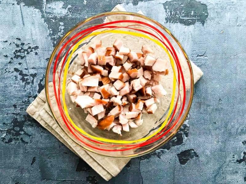 Копченую курицу мелко нарежьте и выложите в глубокую тарелку.