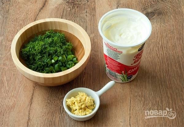 3. Заправьте окрошку сметаной. Для пикантности можно добавить горчицу, предварительно перемешав ее с отложенным желтком до однородной пасты. Вымойте, нарежьте мелко зелень. Влейте в кастрюлю минералку, перемешайте и добавьте зелень.