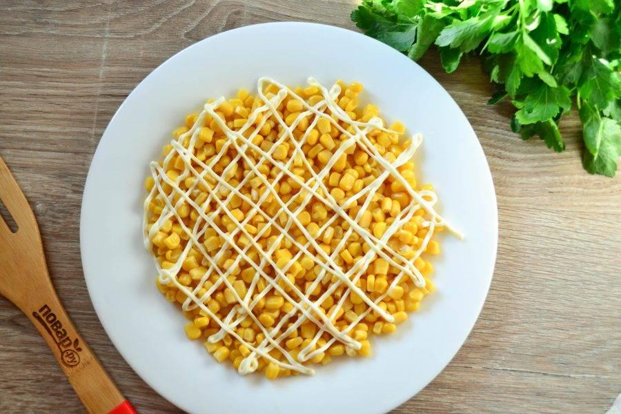 На дно плоской тарелки выложите консервированную кукурузу, которую предварительно необходимо откинуть на дуршлаг, чтобы ушла лишняя жидкость. Сверху кукурузу покройте сеточкой майонеза.