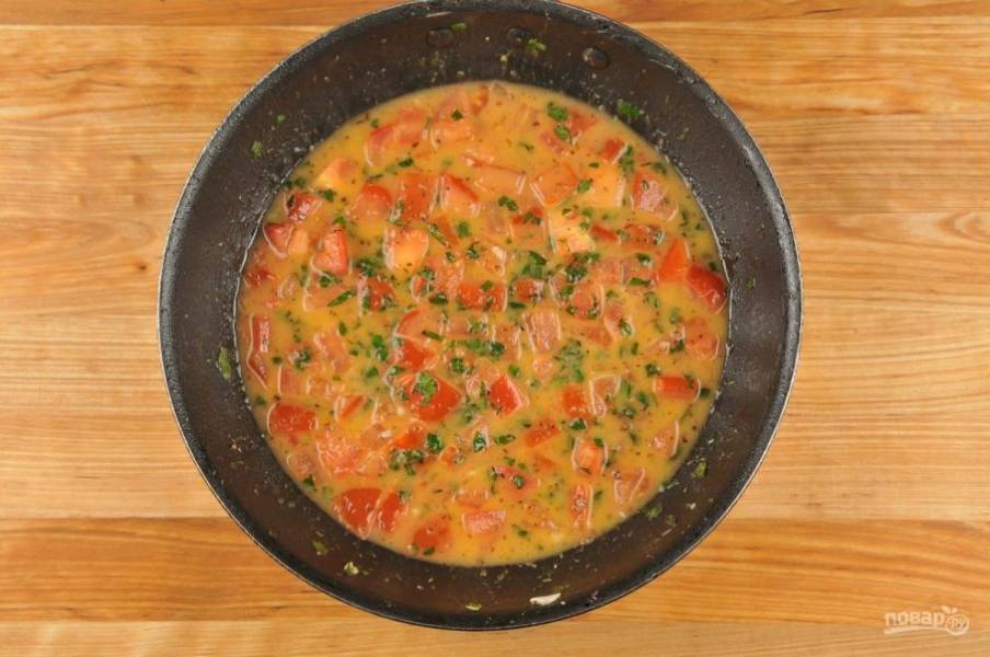 5. Теперь сделайте соус. В сковороде разогрейте масло с чесноком и орегано в течение 30 секунд. Затем влейте воду из-под пасты. Доведите её до кипения. Варите 3 минуты. Потом добавьте помидоры и базилик. Перемешайте и выключите огонь.
