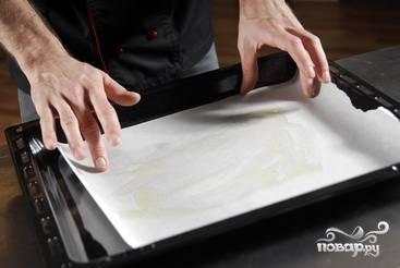 На противень выкладываем бумагу для выпекания и смазываем ее маслом.