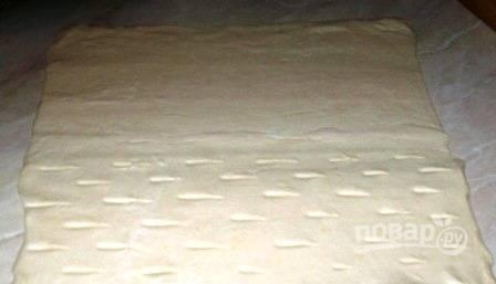 Возьмите замороженное бездрожжевое слоеное тесто и выложите его на рабочую поверхность, чтобы оно разморозилось при комнатной температуре. Если используете замороженную вишню, ее тоже разморозьте. Слегка раскатайте тесто, чтобы получился прямоугольник. Условно разделите тесто на две части. На одной из них сделайте ножом небольшие надрезы длиной в пару сантиметров.