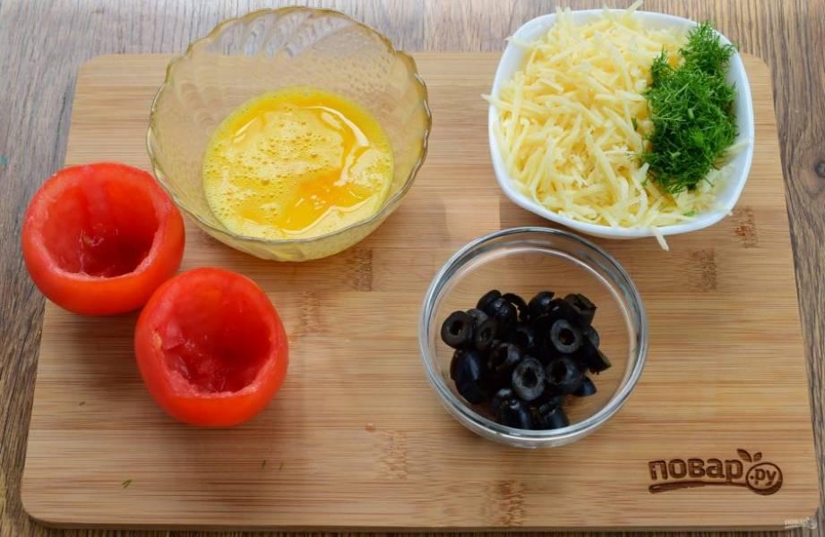 Срежьте верхушку помидоров, с помощью чайной ложки достаньте мякоть. Яйцо слегка взбейте. Маслины нарежьте колечками. Сыр натрите на мелкой терке, зелень измельчите, перемешайте.