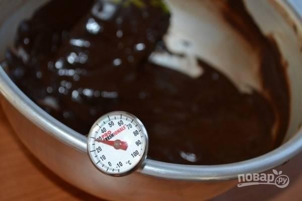 5.Сразу же отделите 2/3 растопленного шоколада (в данном случае это 340 г), а миску с оставшимся растопленным шоколадом снимите с водяной бани. Эти 2/3 шоколада переложите в другую миску, поставьте ее в емкость с ледяной водой, чтобы температура снизилась до 29 градусов. Лучше использовать для работы с горячим шоколадом посуду из нержавеющей стали. Постоянно перемешивая остывающий шоколад лопаткой, старайтесь отделять его от стенок миски.