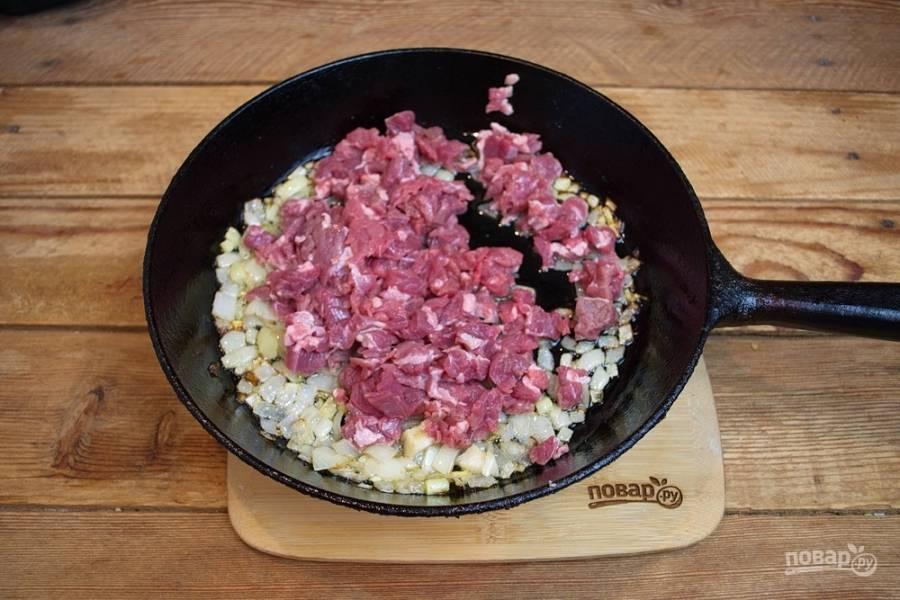 Филейную часть говядины (идеально чистую, без жил) нарежьте ножом на очень мелкие кусочки, почти фарш. Переложите говядину в сковороду и перемешайте с луком. Тушите под крышкой. Время от времени помешивайте, чтоб мясо не подгорело.