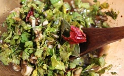 Пока грибы варятся, приготовьте маринад. Для этого в глубокой миске смешайте растительное масло, соевый соус и уксус. Затем добавьте мелко нашинкованную зелень петрушки, кориандр, черный перец, лавровый лист, измельченный чеснок и мелко нарезанный горький перчик чили. Перемешайте, посолите если нужно.