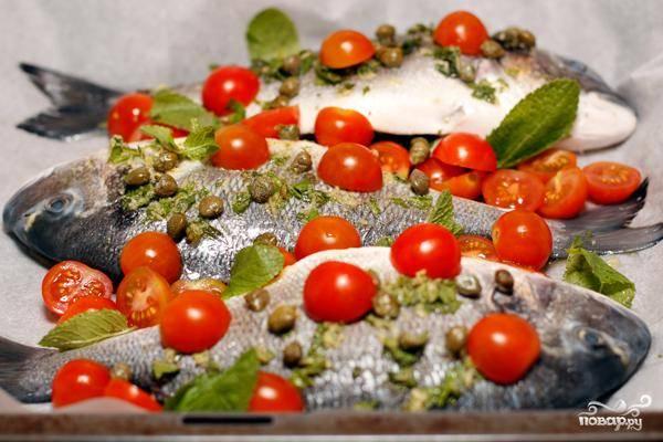 Выкладываем рыбу на противень, предварительно застеленный пергаментной бумагой. Раскладываем сверху каперсы и помидоры черри, если остался маринад - поливаем сверху. Выпекаем 20 минут при 190 градусах - и готово!