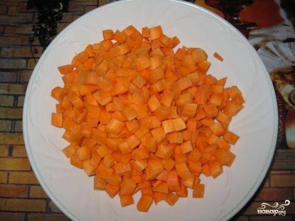Пока мясо готовится, нарезать кубиками морковь.