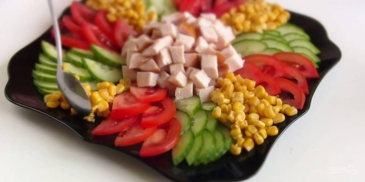 2. Выложите салат в виде солнца: в центр выложите нарезанную куриную грудку, далее аккуратно выложите полукольца огурцов от центра к краям, затем также выложите помидоры. Между огурцами и помидорами выложите кукурузу.