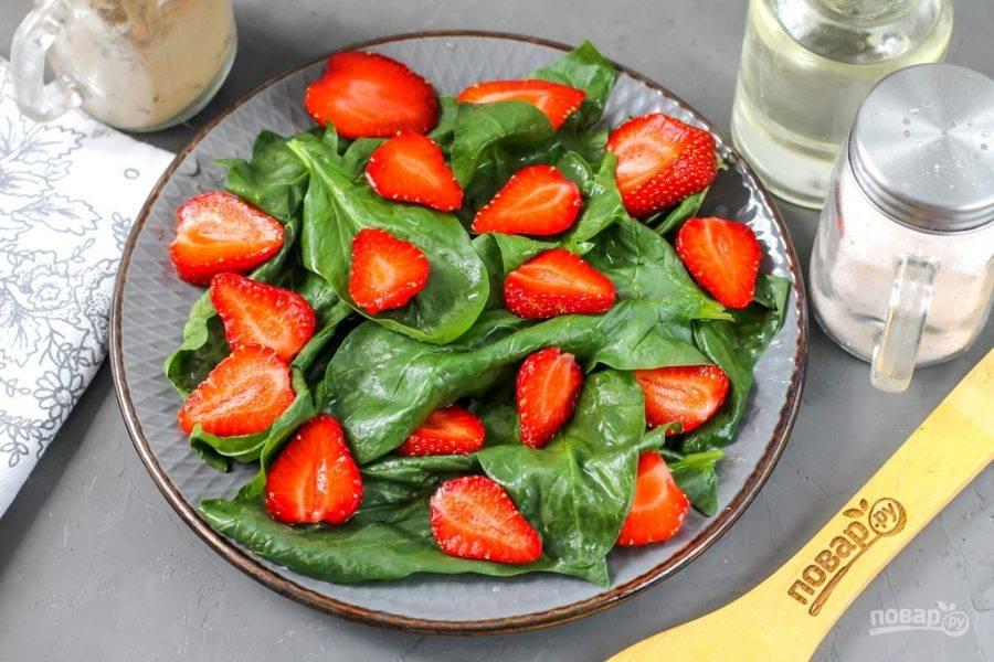 Клубнику промойте в воде и удалите с ягод хвостики. Разрежьте каждую из них пополам или на четыре части, выложите на шпинат.