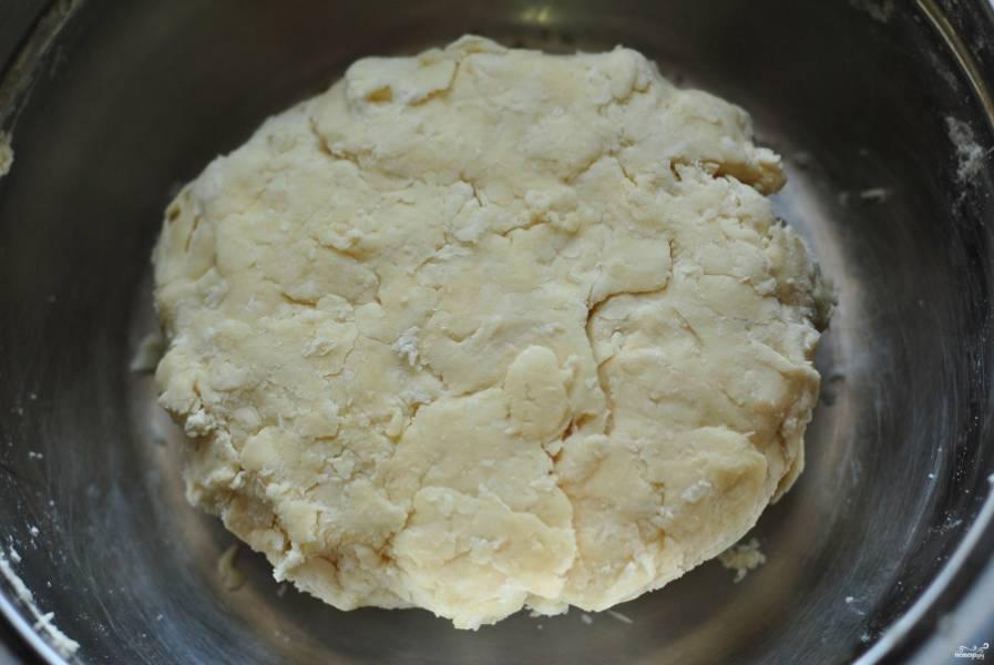 К творогу нужно добавить муку, которую следует просеять. Отправляйте муку в тесто порциями. С первой порцией добавьте соду, погашенную уксусом. Вымешайте тесто руками. Оно должно получиться довольно крутым.