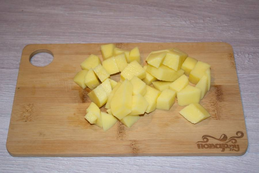 Для приготовления супа со щавлем и яйцом мы возьмем картофель. Очистим его и нарежем кубиком.