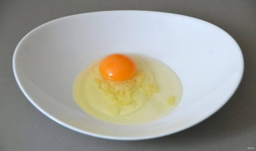 Пока варится бульон приготовьте тесто для клёцек, для этого вбейте в миску одно яйцо, добавьте щепотку соли, натрите на терке чеснок или пропустите его через пресс.