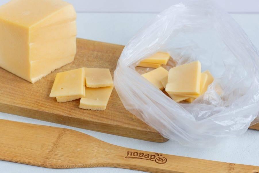 Весь сыр нарежьте тонкими небольшими пластинами и сложите в целый чистый пакет. Завяжите пакет сверху и опустите в кипящую воду, чтобы вода полностью покрывала сыр. Держите пакет с сыром в кипящей воде 5-6 минут, пока сыр не расплавится. Можно придерживать пакет лопаткой, чтобы не всплывал.